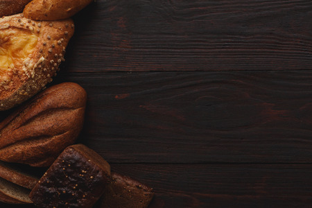 copyspace: Different wholegrain breads on burnished wooden table. Flat lay, above view, chiaroscuro styled