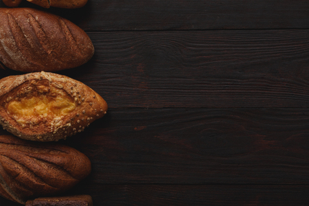 burnished: Different wholegrain breads on burnished wooden table. Flat lay, above view, chiaroscuro styled