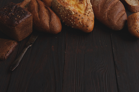copyspace: Different wholegrain breads on burnished wooden table. Elevated view, chiaroscuro styled Stock Photo