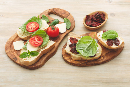 sun dried: Open-faced sandwiches made of ciabatta, sun dried tomatoes, creamy cheese and lettuce leaf basil. Antipasti Stock Photo