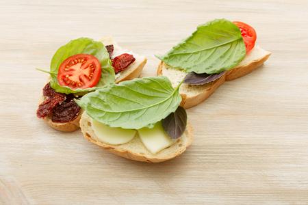 antipasti: Open-faced sandwiches made of ciabatta, sun dried tomatoes, creamy cheese, arugula and lettuce leaf basil. Antipasti