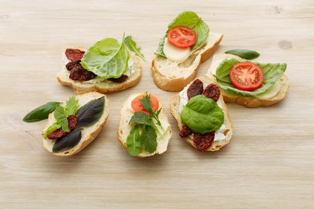 sun dried: Open-faced sandwiches made of ciabatta, sun dried tomatoes, creamy cheese, arugula and lettuce leaf basil. Antipasti