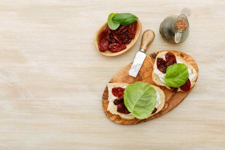 antipasti: Open-faced sandwiches made of ciabatta, sun dried tomatoes, creamy cheese and lettuce leaf basil. Antipasti Stock Photo
