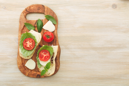 sun dried: Open-faced sandwiches made of ciabatta, sun dried tomatoes, creamy cheese and lettuce leaf basil on a wooden cutboard. Antipasti