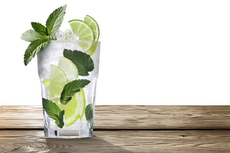 field mint: Mojito (alcoholic cocktail with rum, lime and mint) on wooden table. Clipping paths, infinite depth of field