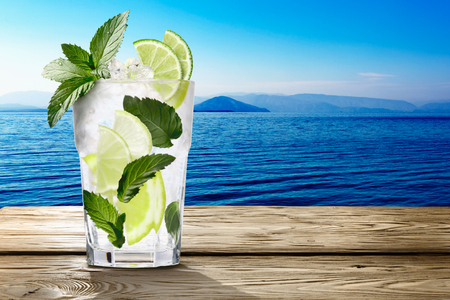 field mint: Mojito (alcoholic cocktail with rum, lime and mint)  in wooden table against seascape. Clipping paths, infinite depth of field
