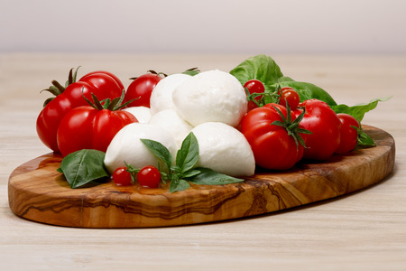 Italian cuisine. Mozzarella, heirloom tomatoes, basil leaves on a wooden serving plate. Large depth of field