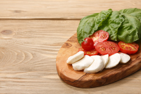 Italian cuisine. Sliced Mozzarella, heirloom tomatoes, basil leaves on a wooden serving plate. Selective focus on cheese