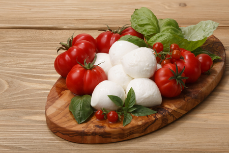 Italian cuisine. Mozzarella, heirloom tomatoes, basil leaves on a wooden serving plate.Large depth of field