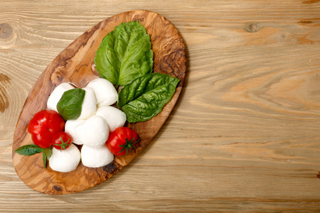Italian cuisine. Mozzarella, heirloom tomatoes, basil leaves on a wooden serving plate. Flat lay