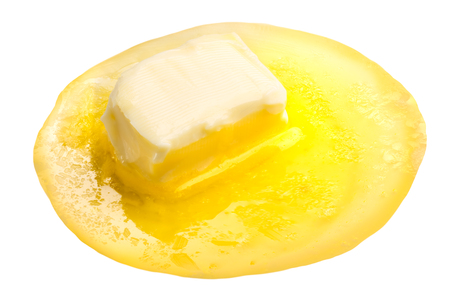 Melted butter with butter piece floating Foto de archivo