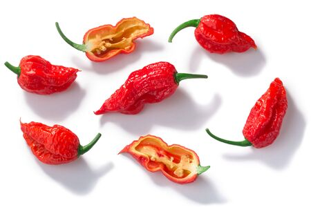 Ghost chile peppers Bhut Jolokia (Capsicum frutescens x Capsicum chinense), whole and halved pods,  isolated, top view Zdjęcie Seryjne