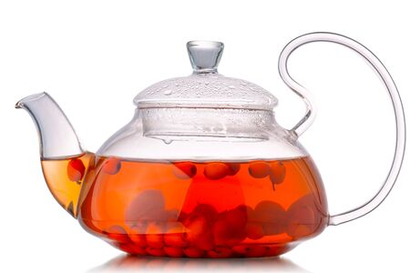 Full glass teapot of Sea buckthorn tea with berries inside, isolated