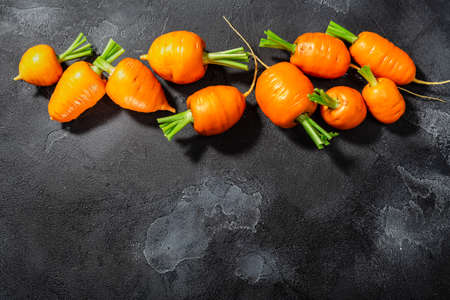 Short Rondo carrots on dark textured background with copy space, top view Zdjęcie Seryjne