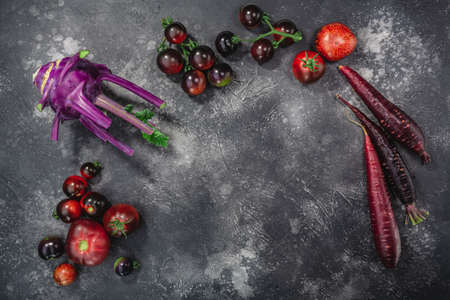 Anthocyanin-rich vegetables on dark textured backdrop, top view
