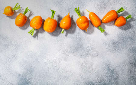 Short Rondo carrots on grey textured background with copy space, top view