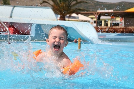 The child laps in an aquapark against waterslides. Stock Photo