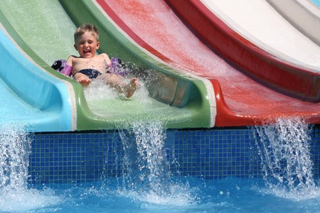 The boy slides a waterslide  in an aquapark. Stock Photo - 7831473