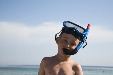 The boy on a beach with an underwater mask and a tube Stock Photo