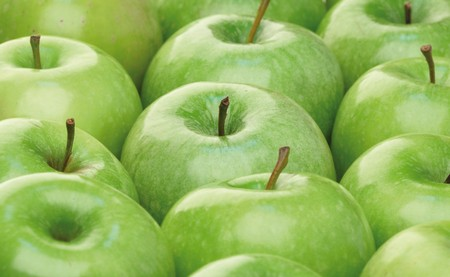 Green apples in an arranged row.
