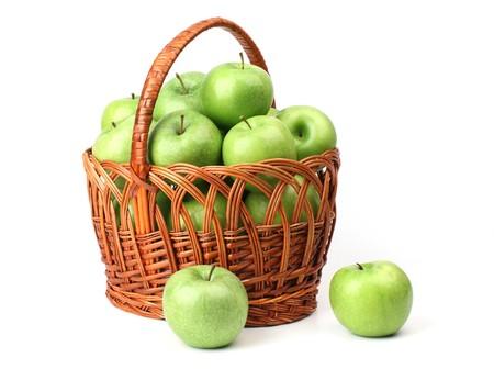 Panier avec des pommes vertes sur un fond blanc.