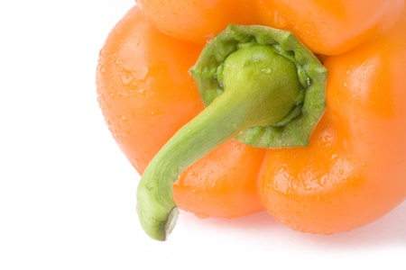 Orange sweet pepper covered with water droplets (on a white background).