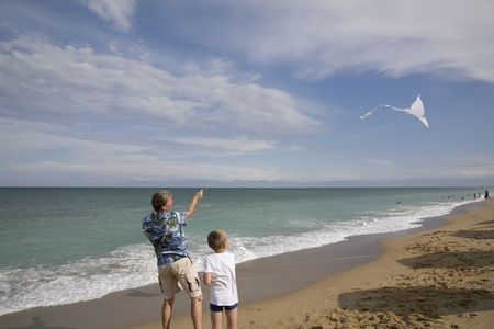The father with the son fly a kite on a beach photo
