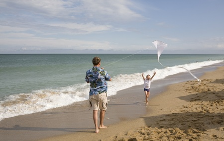 man flying: The father with the son fly a kite on a beach