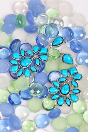 Earrings against color pebbles, costume jewellery