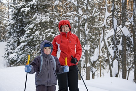 Mum with the son on skis in winter wood photo