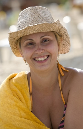 The happy girl in a hat smiles on a beach