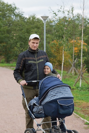 father with two kids walking in the park