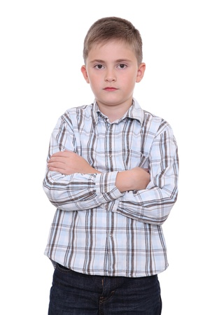 A serious boy stands folding his arms