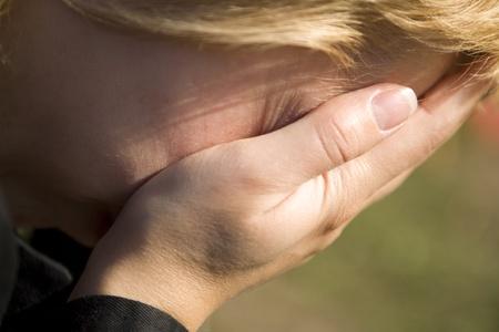 mujer llorando: Ni�a llorando tap�ndose la cara con las manos Foto de archivo