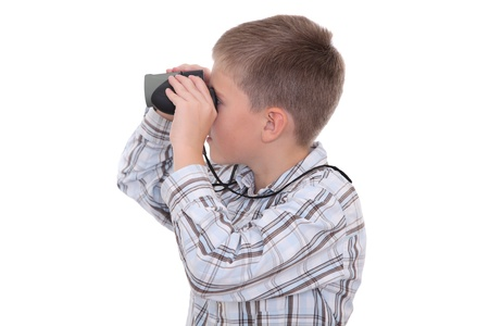 widening: Boy staring into the distance with a help of binoculars, side view