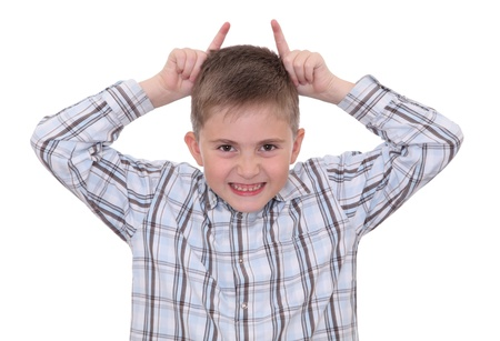 Kidding boy making faces and showing horns sign