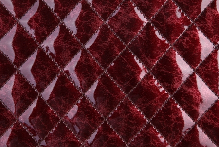 Texture of a red glossy imitation leather with decorative seams Stock Photo