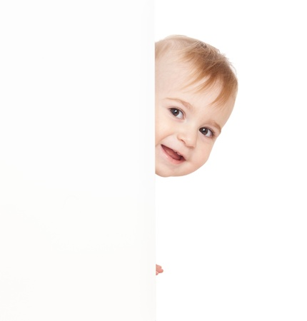 emerge: Baby emerge from behind poster, looks directly,