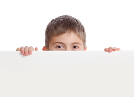 Boy emerge from behind poster, looks directly Stock Photo