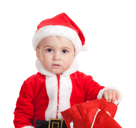 The little boy in a suit of Santa Claus opens a bag gifts