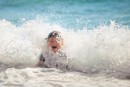 unconcerned: El ni�o nadando en las olas del mar en una playa