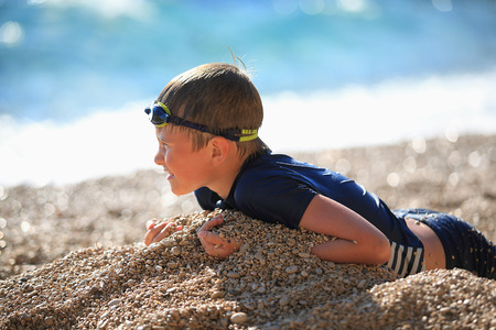unconcerned: The boy lies on a pebble beach after swimming against the sea