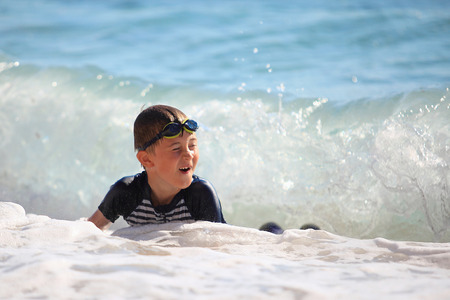 unconcerned: The boy swiming in sea waves on a beach