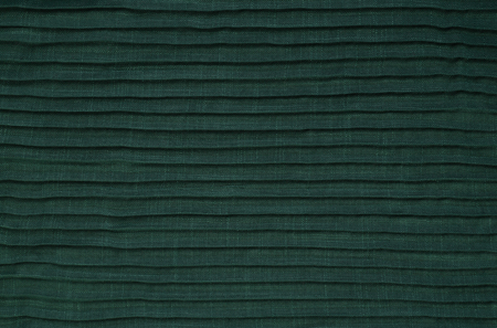 The close up texture of green folded fabric, can be used as a background