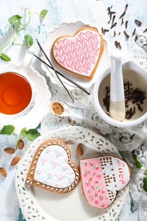Gingerbreads in the form of hearts and tea are served on a table Stock Photo