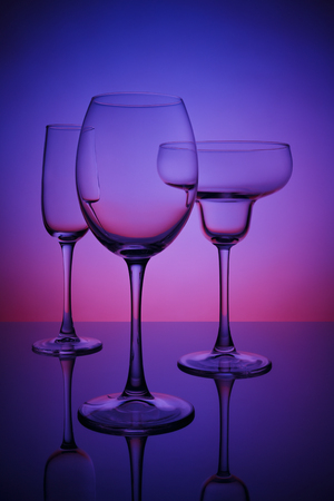 Glasses for drinks on a bar counter, a color neon background Stock Photo
