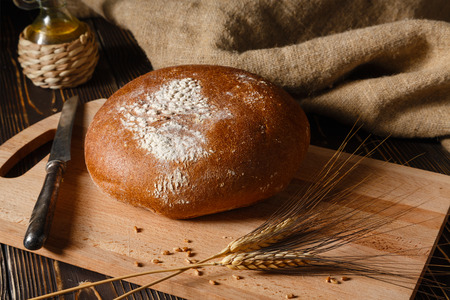 Rural rye bread lies on a table, nearby ear of rye lie.  Stock Photo