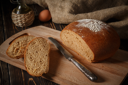 Rye bread lies on a breadboard, two pieces of bread nearby
