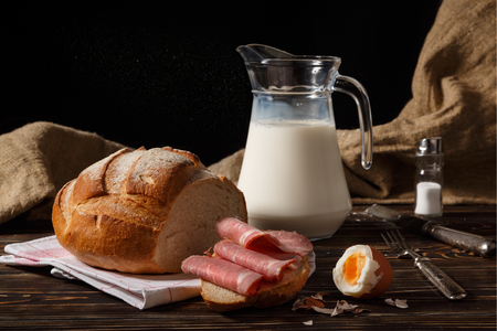 Rural breakfast on a table. Jug with milk, the peeled egg, meat on a piece of white bread.