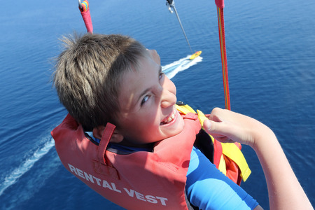 Happy boy parasailing high over the sea. The boat cuts a water smooth surface far below. Having fun. Positive human emotions, feelings, joy. Stock Photo